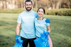 Volunteers portrait with rubbish bags in the park stock photo