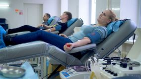 Volunteers prepare to donate blood in a special center, sitting in armchairs. 4K stock footage