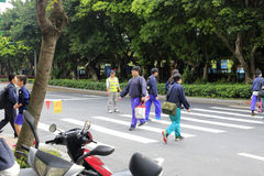 Volunteers protect student crossing the road Royalty Free Stock Photos