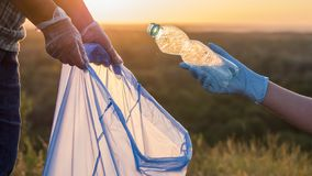 Volunteers put trash in plastic bags. Cleaning the park and caring for the environment