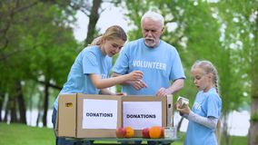 Volunteers putting canned food and fruits donation boxes, poor people assistance. Stock footage stock video