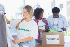 Volunteers putting clothes in clothes rail Stock Images