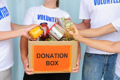 Volunteers putting food in donation box Stock Photography