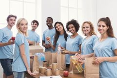 Volunteers putting food and drinks into paper bags. Food sorting. Group of volunteers packing donation for homeless into paper bags, working in office, copy royalty free stock image