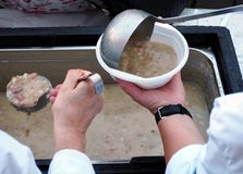 Volunteers serve a hot soup in a plastic dish for poor and homeless stock photography