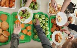 Volunteers serving food for poor people indoors royalty free stock photo