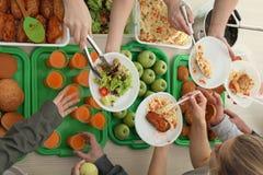 Volunteers serving food for poor people indoors stock image