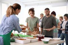 Volunteers serving food for poor people. Indoors royalty free stock photo