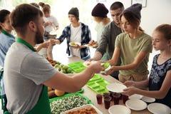 Volunteers serving food for poor people stock photos