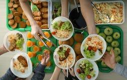 Volunteers serving food for poor people indoors stock images