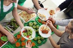 Volunteers serving food for poor people indoors royalty free stock photos