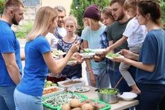 Volunteers serving food for poor people. Outdoors royalty free stock image