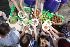 Volunteers serving food for poor people outdoors Royalty Free Stock Photography