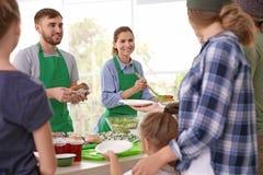 Volunteers serving food for poor people. Indoors stock images