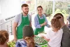 Volunteers serving food for poor people. Indoors royalty free stock image