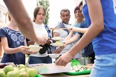 Volunteers serving food for poor people Royalty Free Stock Photography