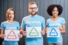 Volunteers with signs of sorting waste. Portrait of three multi ethnic volunteers holding signs of sorting waste standing indoors on the gray wall background Stock Photos