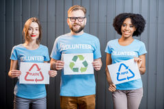 Volunteers with signs of sorting waste. Portrait of three multi ethnic volunteers holding signs of sorting waste standing indoors on the gray wall background royalty free stock images