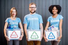 Volunteers with sorted waste. Portrait of three multi ethnic volunteers holding containers with sorted waste standing indoors stock photo