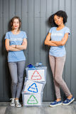 Volunteers with sorted waste. Young female volunteers in blue t-shirts standing with containers with sorted waste indoors stock photo