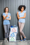 Volunteers with sorted waste. Young female volunteers in blue t-shirts standing with containers with sorted waste indoors royalty free stock images