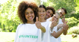 Volunteers standing in a row giving smiling at camera Royalty Free Stock Photography