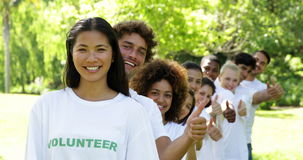 Volunteers standing in a row giving thumbs up to camera Royalty Free Stock Photography