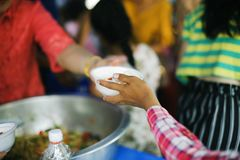Volunteers submit delicious food to the poor : Helping the poor in society by donating food : The concept of hunger.  stock photos