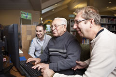 Volunteers teaching a senior how to use a computer.  Royalty Free Stock Image