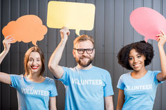 Volunteers with thought bubbles. Volunteers holding colorful thought bubbles standing on the gray wall background Royalty Free Stock Images