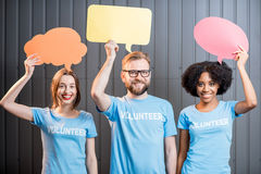 Volunteers with thought bubbles. Volunteers holding colorful thought bubbles standing on the gray wall background Stock Photos