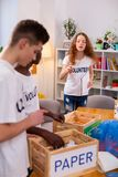 Volunteers wearing white t-shirts sorting litter together royalty free stock photography