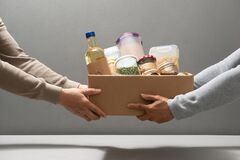 Free Volunteers With Donation Box With Foodstuffs On Grey Background Royalty Free Stock Image - 194642626