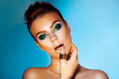 Voluptuous adult woman with green colors makeup on blue backgrou Royalty Free Stock Images
