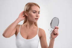 Voluptuous blond girl looking at her appearance. Sensual young woman is posing in front of mirror. She is standing and touching her hair with satisfaction Stock Photography