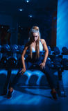 Voluptuous blonde woman sit on dumbbell Royalty Free Stock Image