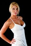 Voluptuous and fit. Beautiful blonde woman poses wearing white tank top and shorts Stock Photography