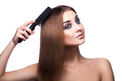 Voluptuous girl with blue eyes combing her perfect healthy strei. Ght brown hair with comb on white background in studio. isolated Stock Photo