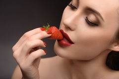 Voluptuous girl eating red berry. Sexy young woman is tasting sweet strawberry with temptation. Isolated Stock Image