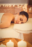 Voluptuous girl enjoying spa treatment. Tranquil young woman is lying on massage bed near burning candles at beauty salon. Her eyes are closed with pleasure Royalty Free Stock Image