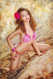 Voluptuous girl in pink bikini with red flower Stock Photo