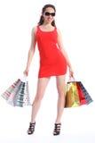 Voluptuous lange mit Beinen versehene Frau hält Einkaufenbeutel an Stockfotos