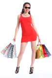 Voluptuous long legged woman holds shopping bags. In dark sunglasses a beautiful voluptuous young caucasian woman with long legs wearing short red dress Stock Photos