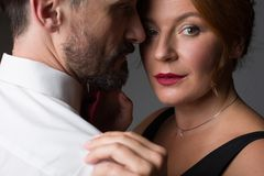 Voluptuous married couple hugging with passion. Close up portrait of sensual middle-aged women embracing her husband gently. Man is looking at wife with desire Royalty Free Stock Photography