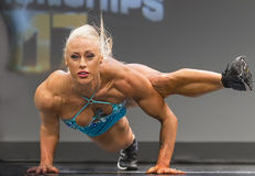 Voluptuous Pro Fitness Gal Performs Athletic Maneuvers. Gorgeous Missy Farrell demonstrates power and flexibility during her pro fitness stage routine at the Stock Image