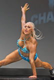 Voluptuous Pro Fitness Gal Performs Athletic Maneuvers. Gorgeous Missy Farrell demonstrates power and flexibility during her pro fitness stage routine at the Royalty Free Stock Photography
