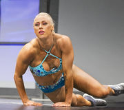 Voluptuous Pro Fitness Gal Performs Athletic Maneuvers. Gorgeous Missy Farrell demonstrates power and flexibility during her pro fitness stage routine at the Royalty Free Stock Images