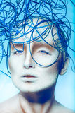 Voluptuous woman with creative decoration on head. In studio on blue background Royalty Free Stock Images