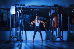 Voluptuous woman doing exercises in gym. Near mirror Stock Photography