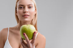 Voluptuous woman eating vitamins with pleasure. Eat this fruit. Confident young girl is showing apple to camera. Isolated and copy space in right side Royalty Free Stock Photo